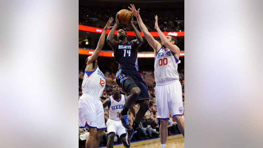 Charlotte Bobcats' Michael Kidd-Gilchrist (14) shoots over Philadelphia 76ers' Spencer Hawes (00) and Evan Turner (12) during the first half of an NBA basketball game, Saturday, Feb. 9, 2013, in Philadelphia. (AP Photo/Michael Perez)