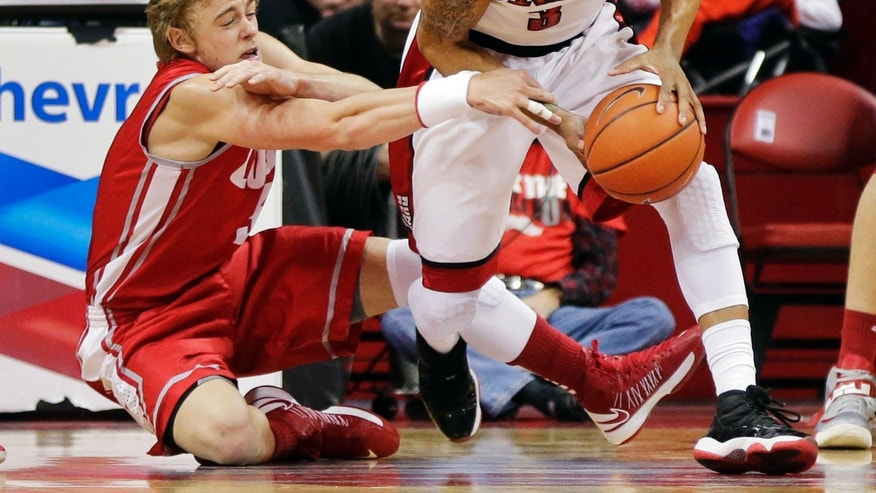 New Mexico's Hugh Greenwood, left, tries to strip UNLV's Anthony Marshall of the ball in the first half of an NCAA college basketball game, Saturday, Feb. 9, 2013, in Las Vegas. (AP Photo/Julie Jacobson)