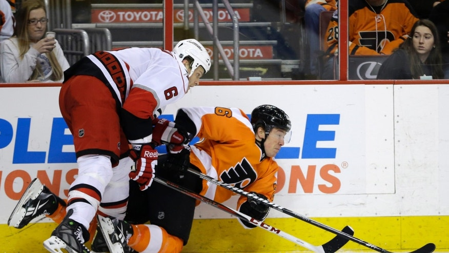 Philadelphia Flyers' Ruslan Fedotenko, right, of Ukraine, and Carolina Hurricanes' Tim Gleason reach for the puck during the second period of an NHL hockey game, Saturday, Feb. 9, 2013, in Philadelphia. (AP Photo/Matt Slocum)