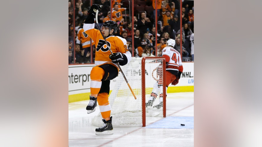 Philadelphia Flyers' Matt Read, left, celebrates after scoring a goal as Carolina Hurricanes' Jay Harrison skates off during the second period of an NHL hockey game, Saturday, Feb. 9, 2013, in Philadelphia. (AP Photo/Matt Slocum)