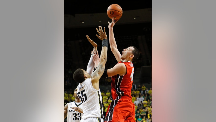 Utah's Jeremy Olsen, right, shots over Oregon's Tony Woods during the first half of an NCAA college basketball game in Eugene, Ore., Saturday Feb. 9, 2013. (AP Photo/Chris Pietsch)
