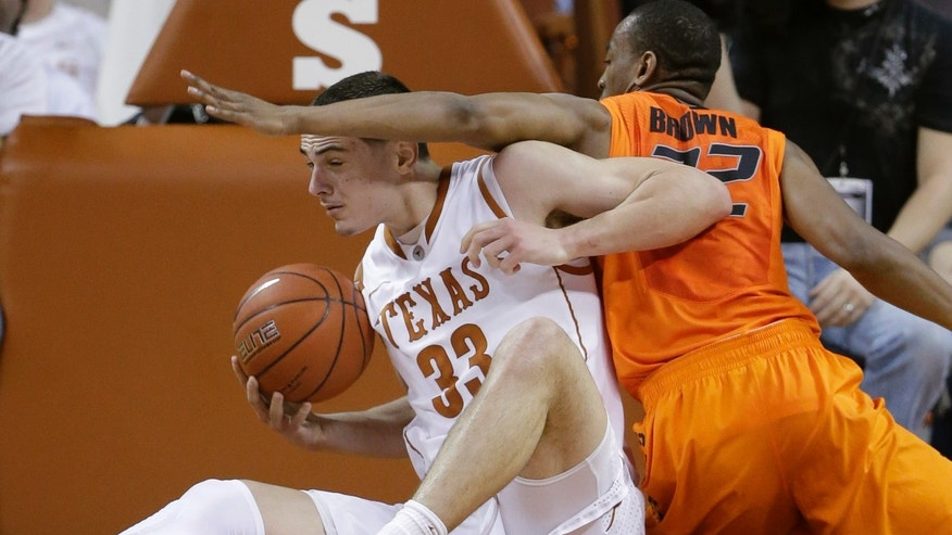 Texas' Ioannis Papapetrou (33) and Oklahoma State's Markel Brown, right, scramble for a loose ball during the first half of an NCAA college basketball game, Saturday, Feb. 9, 2013, in Austin, Texas. (AP Photo/Eric Gay)