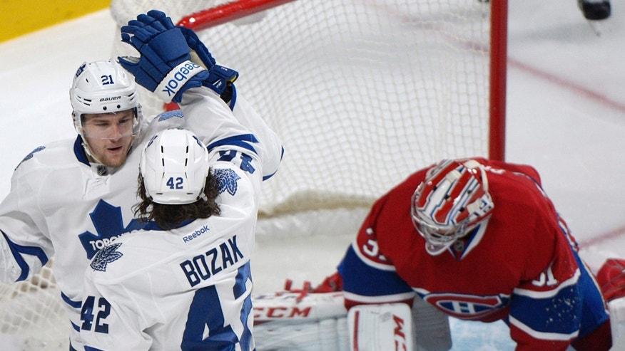 Toronto Maple Leafs' James van Riemsdyk, left, celebrates with teammate Tyler Bozak after scoring against Montreal Canadiens goaltender Carey Price during the second period of an NHL hockey game in Montreal, Saturday, Feb. 9, 2013. (AP Photo/The Canadian Press, Graham Hughes)