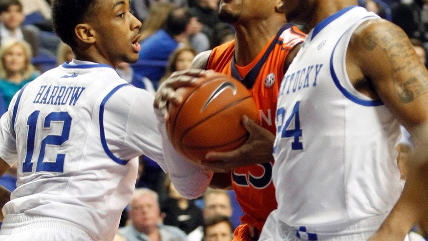 Auburns's Noel Johnson, middle, looks for an opening between Kentucky's Ryan Harrow (12) and Julius Mays during the first half of an NCAA college basketball game at Rupp Arena in Lexington, Ky., Saturday, Feb. 9, 2013. (AP Photo/James Crisp)