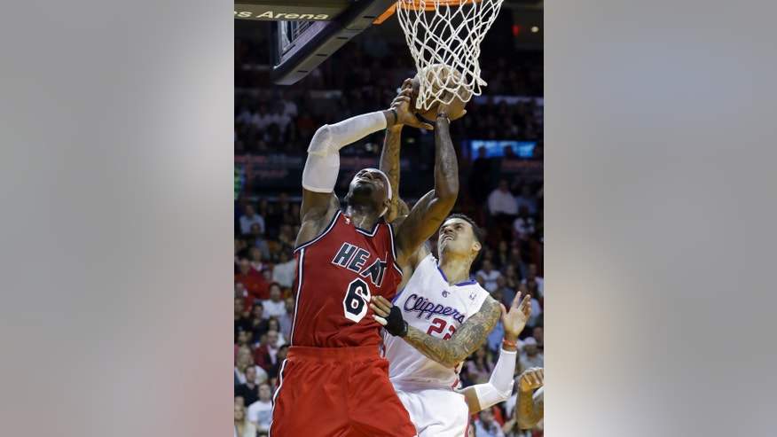 Miami Heat's LeBron James (6) is fouled by Los Angeles Clippers' Matt Barnes (22) during the second half of an NBA basketball game in Miami, Friday, Feb. 8, 2013. The Heat won 111-89. (AP Photo/Alan Diaz)