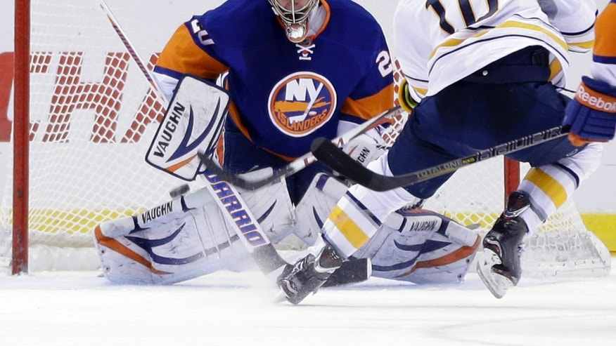 Buffalo Sabres' Christian Ehrhoff, right, scores a goal past New York Islanders goalie Evgeni Nabokov during the second period of the NHL hockey game Saturday, Feb. 9, 2013, in Uniondale, N.Y. (AP Photo/Seth Wenig)