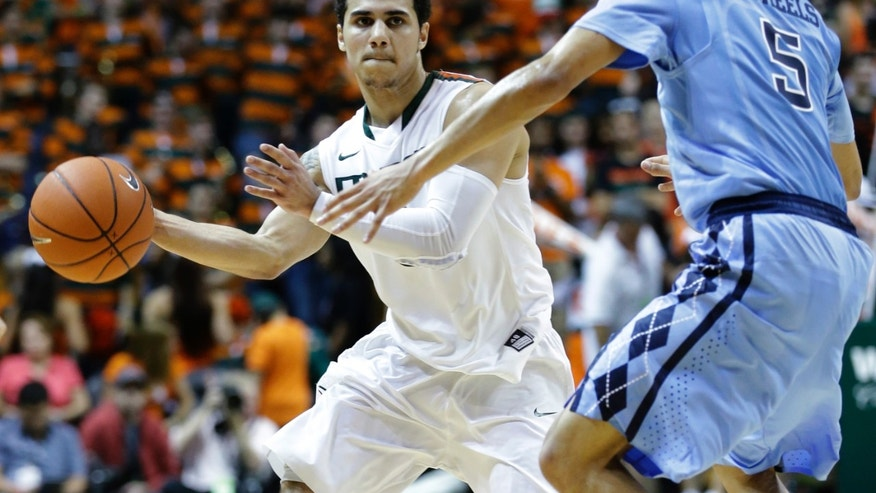 Miami guard Shane Larkin passes past North Carolina guard Marcus Paige (5) during the first half of an NCCA college basketball game, Saturday, Feb. 9, 2013, in Coral Gables, Fla. (AP Photo/Wilfredo Lee)