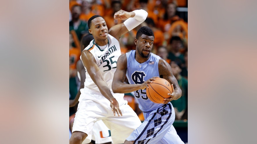 North Carolina's Reggie Bullock, foreground, looks for an open teammate as Miami's Kenny Kadji defends during the first half of an NCCA college basketball game, Saturday, Feb. 9, 2013, in Coral Gables, Fla. (AP Photo/Wilfredo Lee)