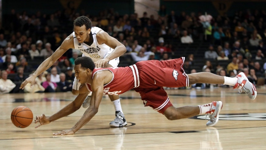 Arkansas guard Michael Qualls, front, and Vanderbilt guard Kevin Bright (15) dive for a loose ball during the first half of an NCAA college basketball game Saturday, Feb. 9, 2013, in Nashville, Tenn. (AP Photo/Mark Humphrey)