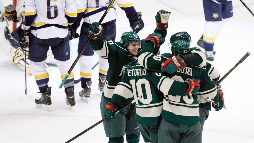 Minnesota Wild left wing Zach Parise (11) celebrates with teammates Devin Setoguchi (10), Ryan Suter (20) and Mikko Koivu, of Finland, after Setoguchi scored the game-winning goal against Nashville Predators goalie Chris Mason with assists by Suter and Koivu during overtime of an NHL hockey game Saturday, Feb. 9, 2013 in St. Paul, Minn. The Wild won 2-1. (AP Photo/Genevieve Ross)