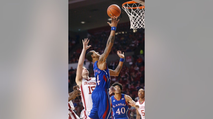 Kansas guard Travis Releford goes up for a shot in front of Oklahoma forward Tyler Neal (15) and Kansas' Kevin Young (40) during the first half of an NCAA college basketball game in Norman, Okla., Saturday, Feb. 9, 2013. (AP Photo/Sue Ogrocki)