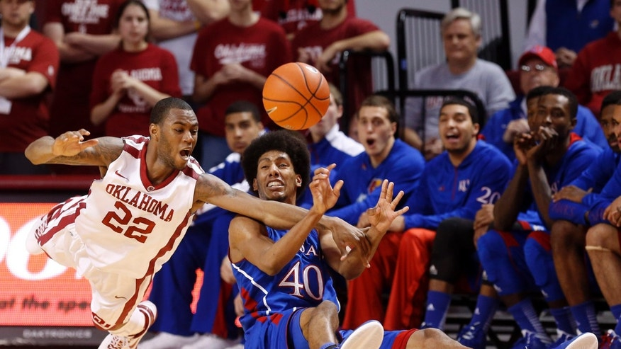 Oklahoma forward Amath M'Baye (22) reaches for the ball as Kansas forward Kevin Young passes it during the first half of an NCAA college basketball game in Norman, Okla., Saturday, Feb. 9, 2013. (AP Photo/Sue Ogrocki)