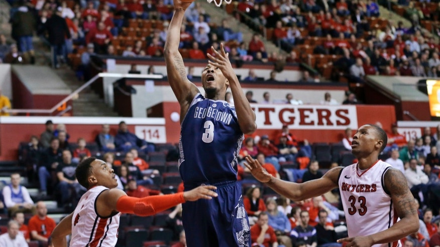 Georgetown's Mikael Hopkins (3) takes a shot as he splits Rutgers defenders Myles Mack and Wally Judge (33) during the first half of an NCAA college basketball game Saturday, Feb. 9, 2013, in Piscataway, N.J. (AP Photo/Mel Evans)
