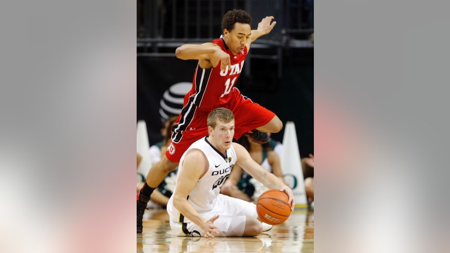 Utah's Renan Lenz, top, jumps over Oregon's E.J. Singler as he dives for a loose ball during the second half in an NCAA college basketball game in Eugene, Ore., Saturday, Feb. 9, 2013. (AP Photo/Chris Pietsch)