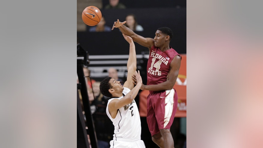 Florida State's Robert Gilchrist (14) passes the ball over Wake Forest's Devin Thomas (2) during the first half of an NCAA college basketball game in Winston-Salem, N.C., Saturday, Feb. 9, 2013. (AP Photo/Chuck Burton)