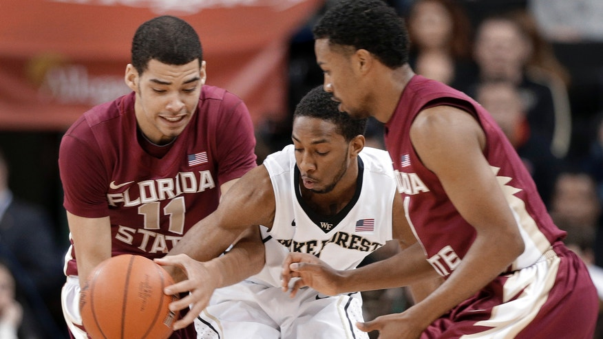 Wake Forest's Madison Jones, center, and Florida State's Kiel Turpin, left, and Devon Bookert, right, look for control of the ball during the first half of an NCAA college basketball game in Winston-Salem, N.C., Saturday, Feb. 9, 2013. (AP Photo/Chuck Burton)