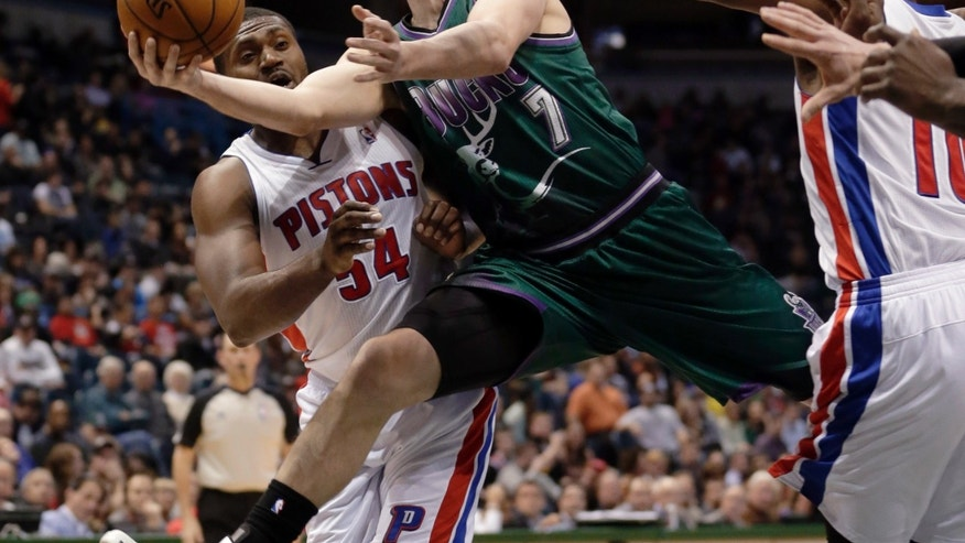Milwaukee Bucks' Ersan Ilyasova is fouled as he drives between Detroit Pistons' Jason Maxiell (54) and Greg Monroe during the second half of an NBA basketball game Saturday, Feb. 9, 2013, in Milwaukee. (AP Photo/Morry Gash)