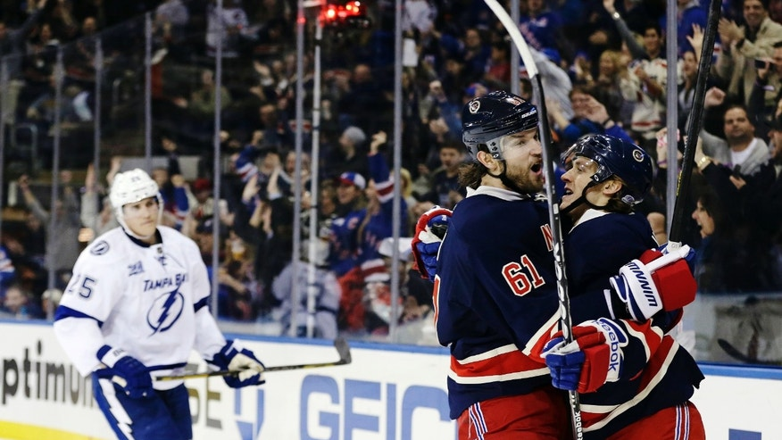 New York Rangers left wing Rick Nash (61) hugs Carl Hagelin (62) as Tampa Bay Lightning's Matt Carle (25) reacts after Hagelin scored a goal during the second period of an NHL hockey game, Sunday, Feb. 10, 2013, in New York. (AP Photo/Frank Franklin II)