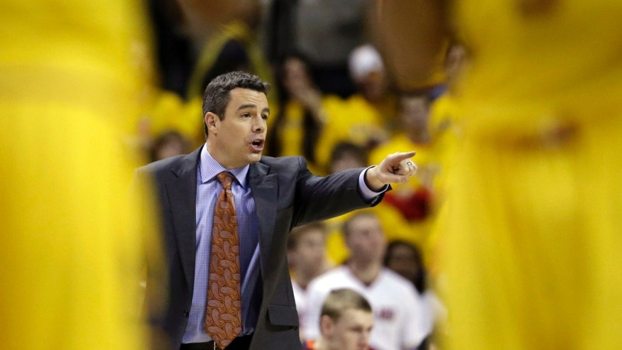 Virginia head coach Tony Bennett gestures near a pair of Maryland players as he directs his team in the first half of an NCAA college basketball game in College Park, Md., Sunday, Feb. 10, 2013. (AP Photo/Patrick Semansky)