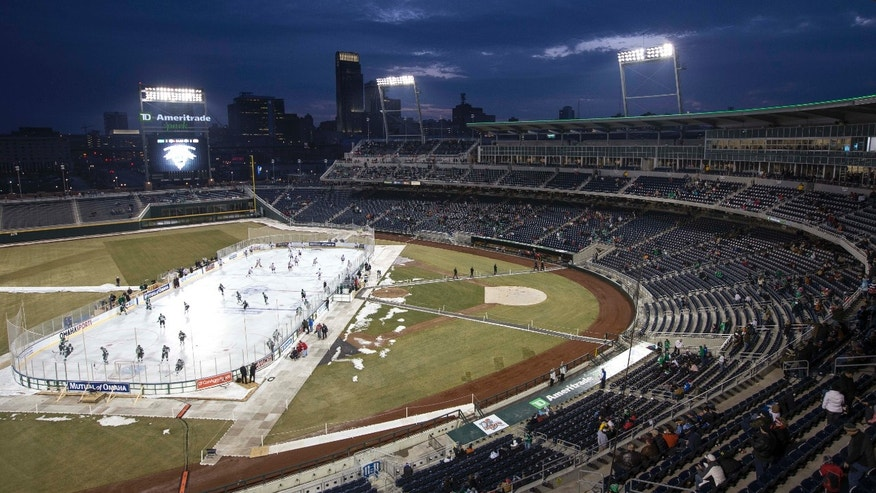 North Dakota and Nebraska-Omaha players warm for a college hockey game held outdoors in Omaha, Neb., Saturday, Feb. 9, 2013. The rink sits between what would be first and third bases at TD Ameritrade Park, the stadium where the College World Series is played each June. (AP Photo/Nati Harnik)