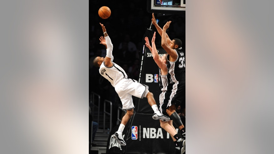 Brooklyn Nets' C.J. Watson (1) leaps backward to shoot over San Antonio Spurs' Nando de Colo (25) and Boris Diaw (33) in the second half of an NBA basketball game, Sunday, Feb. 10, 2013, at Barclays Center in New York. The Spurs won 111-86. (AP Photo/Kathy Kmonicek)
