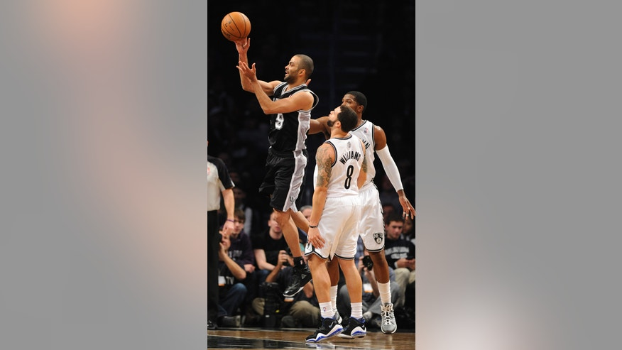 San Antonio Spurs' Tony Parker (9) shoots past Brooklyn Nets' Deron Williams (8) and Joe Johnson in the first half of an NBA basketball game, Sunday, Feb. 10, 2013, at Barclays Center in New York. The Spurs won 111-86. (AP Photo/Kathy Kmonicek)