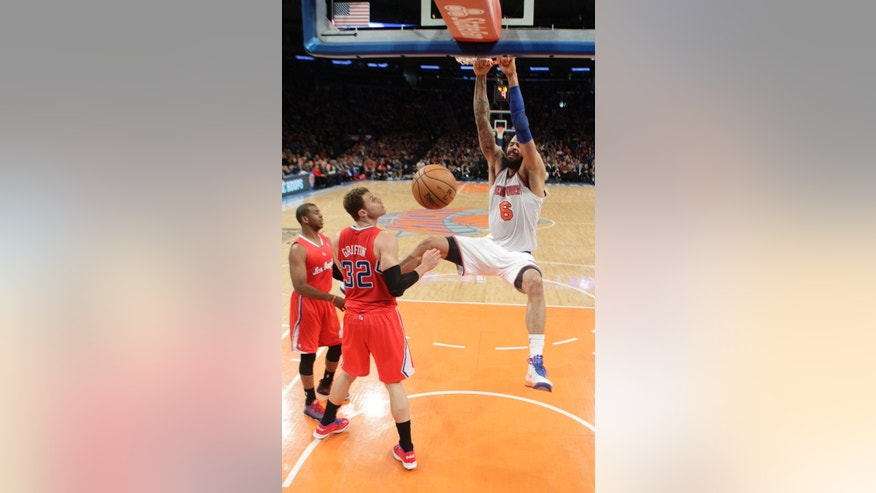 New York Knicks' Tyson Chandler (6) dunks the ball as Los Angeles Clippers' Blake Griffin (32) and teammate Chris Paul looks on during the first half of an NBA basketball game Sunday, Feb. 10, 2013, in New York.  (AP Photo/Frank Franklin II)