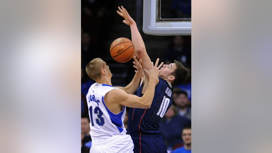 Connecticut's Tyler Olander, right, blocks a hsot by Seton Hall's Haralds Karlis during the first half of an NCAA college basketball game Sunday, Feb. 10, 2013, in Newark, N.J. (AP Photo/Bill Kostroun)