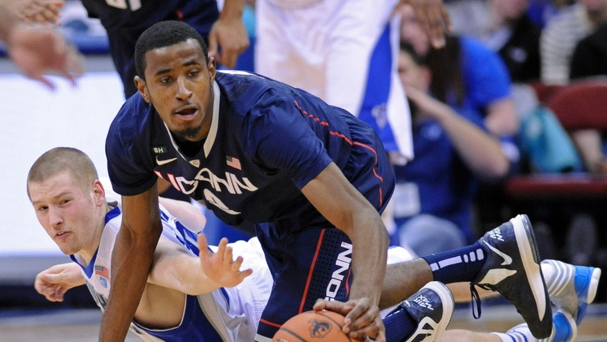 Connecticut's Deandre Daniels, right, beats Seton Hall's Kyle Smyth to a loose ball during the first half of an NCAA college basketball game on Sunday, Feb. 10, 2013, in Newark, N.J. (AP Photo/Bill Kostroun)