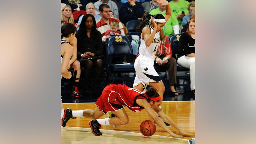 Louisville guard Bria Smith, bottom, is tripped up by Notre Dame guard Skylar Diggins in the first half of an NCAA college basketball game, Monday, Feb. 11, 2013, in South Bend, Ind. (AP Photo/Joe Raymond)