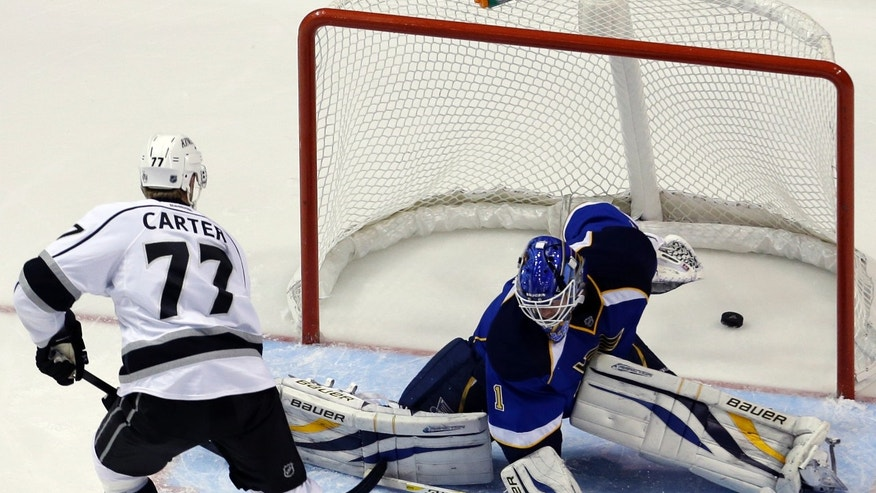 Los Angeles Kings' Jeff Carter, left, scores his second goal of an NHL hockey game past St. Louis Blues goalie Brian Elliott during the second period, Monday, Feb. 11, 2013, in St. Louis. (AP Photo/Jeff Roberson)