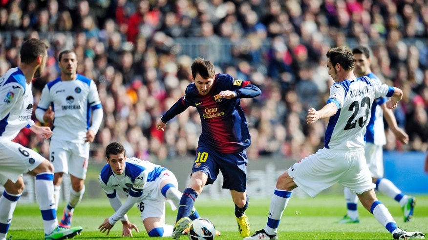FC Barcelona's Lionel Messi from Argentina, center, duels for the ball against Getafe's Alberto Lopo, center left, and Borja Fernandez, right, during a Spanish La Liga soccer match, at the Camp Nou stadium in Barcelona, Spain, Sunday, Feb. 10, 2013. (AP Photo/Manu Fernandez)
