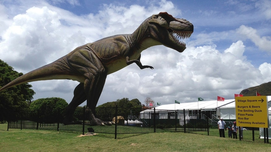 FILE - In this Dec. 11, 2012 file photo, people stand near an eight-meter (26-foot) replica of a tyrannosaurus rex standing between the 9th green and the 10th tee at the Sunshine Coast resort course in south Queensland, Australia.  The PGA of Australia confirmed, Monday, Feb. 11, 2013,  it will move the venue of its PGA Championship, which was overshadowed last year by the billionaire resort owner's decision to position a giant robotic dinosaur outside the clubhouse and post unusual signage around the course. (AP Photo/Dennis Passa, File)