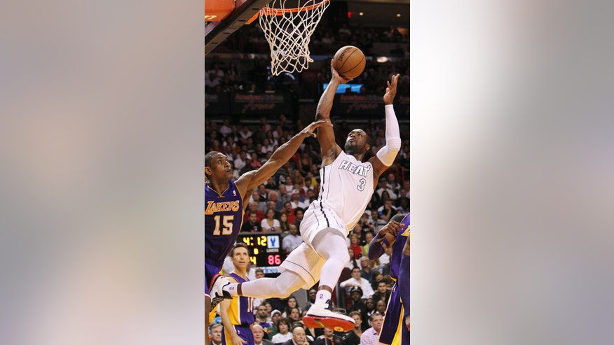 Miami Heat's Dwyane Wade (3) goes to the basket against Los Angeles Lakers' Metta World Peace (15) during the fourth quarter of their NBA basketball game, Sunday, Feb. 10, 2013, in Miami. The Heat won 107-97. (AP Photo/El Nuevo Herald, David Santiago)  MAGS OUT