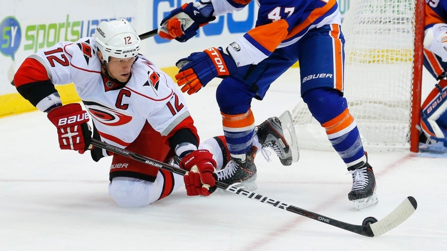 Carolina Hurricanes center Eric Staal (12) passes the puck out to a teammate in front of New York Islanders' Andrew MacDonald (47) during the first period of an NHL hockey game at the Nassau Coliseum in Uniondale, N.Y., Monday, Feb.11, 2013. (AP Photo/Paul J. Bereswill)