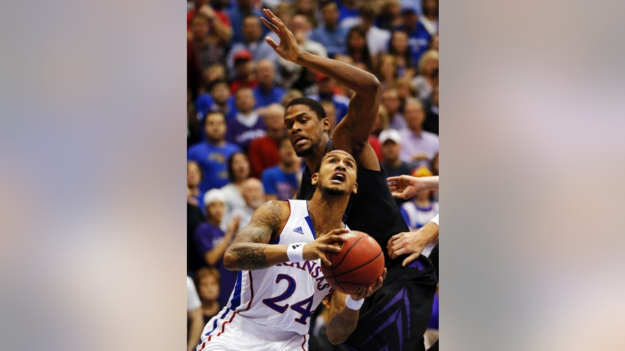 Kansas guard Travis Releford (24) drives past Kansas State forward Jordan Henriquez, back, during the first half of an NCAA college basketball game in Lawrence, Kan., Monday, Feb. 11, 2013. (AP Photo/Orlin Wagner)