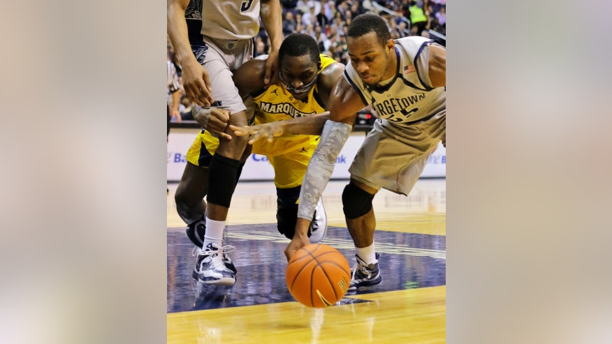 Marquette center Chris Otule (42) gets tangled up around the leg of Georgetown forward Mikael Hopkins (3) as he goes for the ball with guard Jabril Trawick (55) during the first half of an NCAA college basketball game, Monday, Feb. 11, 2013, in Washington. (AP Photo/Alex Brandon)