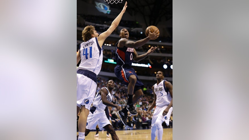 Atlanta Hawks guard Jeff Teague (0) scores past Dallas Mavericks' Dirk Nowitzki (41), of Germany, as teammates Bernard James (5) and Rodrigue Beaubois look on during the first half of an NBA basketball game, Monday, Feb. 11, 2013, in Dallas. (AP Photo/LM Otero)