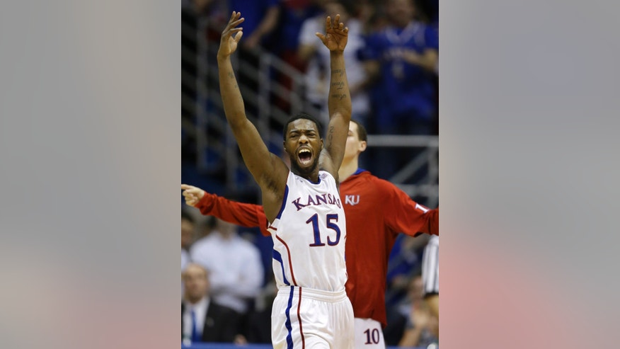 Kansas guard Elijah Johnson (15) celebrates at a timeout during the second half of an NCAA college basketball game against Kansas State in Lawrence, Kan., Monday, Feb. 11, 2013. Kansas defeated Kansas State 83-62. (AP Photo/Orlin Wagner)