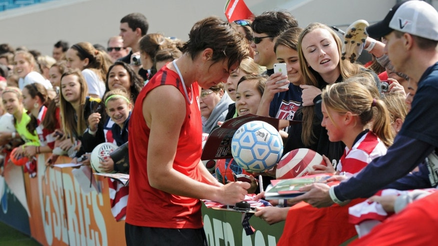 Abby Wambach signs autographs for fans after the U.S. women's soccer team practiced in Jacksonville, Fla., on Friday, Feb. 8, 2013. The practice was open to the public, and several hundred people attended. (AP Photo/The Florida Times-Union, Bob Mack)