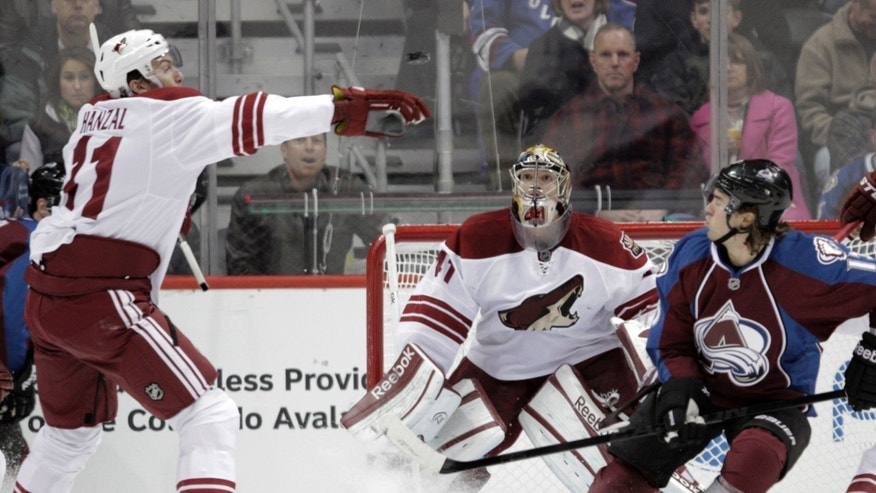 Phoenix Coyotes center Martin Hanzal (11) reaches for the puck as Phoenix Coyotes goalie Mike Smith (41) and Colorado Avalanche right wing P.A. Parenteau (15) watch during the first period of an NHL hockey game, Monday, Feb. 11, 2013, in Denver. (AP Photo/Joe Mahoney)