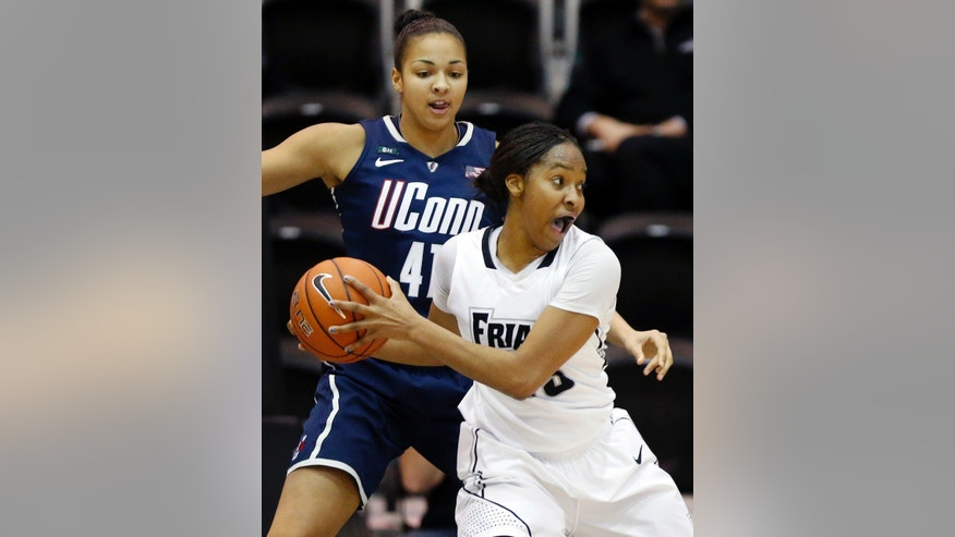 Providence's Brianna Edwards, right, looks to pass in front of Connecticut's Kiah Stokes (41) in the first half of an NCAA college basketball game in Providence, R.I., Tuesday, Feb. 12, 2013. (AP Photo/Michael Dwyer)