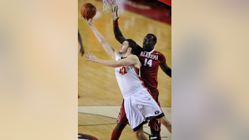 Georgia forward Nemanja Djurisic (42) scores a lay up while defenede by Alabama center Moussa Gueye (14) during the first half of an NCAA college basketball game in Athens, Ga., Tuesday, Feb. 12, 2013. (AP Photo/The Athens Banner-Herald, AJ Reynolds)MANDATORY CREDIT