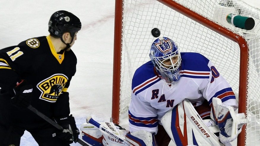 Boston Bruins center Gregory Campbell (11) watches as the puck goes in the net past New York Rangers goalie Henrik Lundqvist (30) during the third period of an NHL hockey game in Boston, Tuesday, Feb. 12, 2013. The goal was scored by Boston Bruins left wing Brad Marchand (63).  (AP Photo/Elise Amendola)