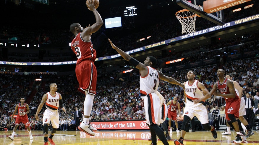 Miami Heat's Dwyane Wade (3) shoots against Portland Trail Blazers' Wesley Matthews (2) during the first half of an NBA basketball game in Miami, Tuesday, Feb. 12, 2013. (AP Photo/Alan Diaz)