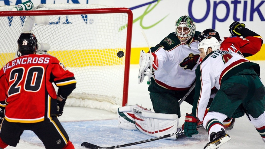 Minnesota Wild goalie Niklas Backstrom, center, of Finland, and Clayton Stoner, right, watch the puck as they defend against Calgary Flames' Curtis Glencross during the second period of their NHL hockey game, Monday, Feb. 11, 2013, in Calgary, Alberta. (AP Photo/The Canadian Press, Jeff McIntosh)