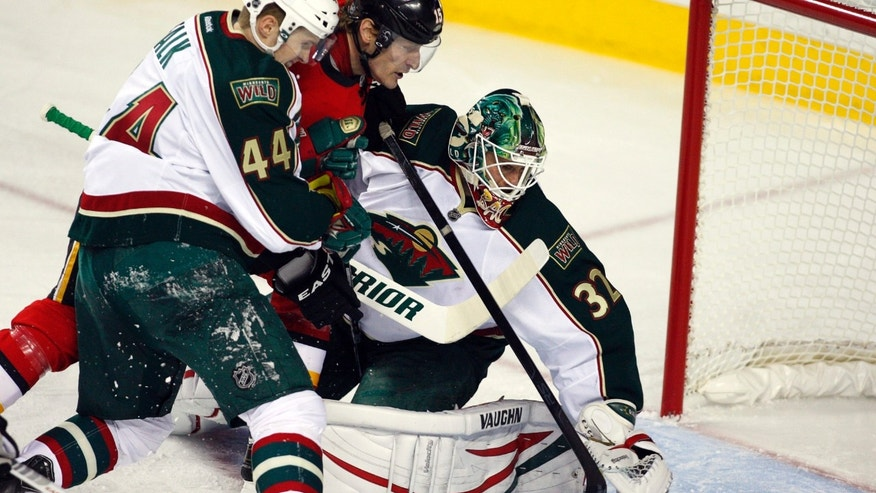 Minnesota Wild goalie Niklas Backstrom, right, of Finland, dives towards the puck as Justin Falk, left, checks Calgary Flames' Tim Jackman during the first period of their NHL hockey game, Monday, Feb. 11, 2013, in Calgary, Alberta. (AP Photo/The Canadian Press, Jeff McIntosh)