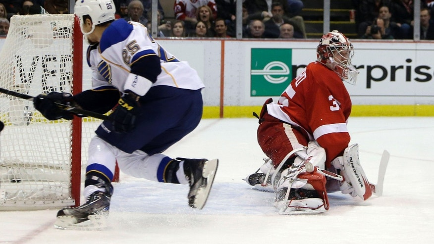 St. Louis Blues right wing Chris Stewart (25) gets the puck past Detroit Red Wings goalie Jimmy Howard (35) during the second period of an NHL hockey game in Detroit, Wednesday, Feb. 13, 2013. (AP Photo/Carlos Osorio)