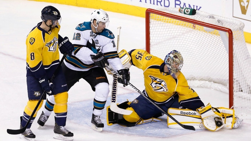 Nashville Predators goalie Pekka Rinne (35), of Finland, gloves a shot as San Jose Sharks center Patrick Marleau (12) reaches for the rebound in the second period of an NHL hockey game Tuesday, Feb. 12, 2013, in Nashville, Tenn. At left is Predators defenseman Kevin Klein. (AP Photo/Mark Humphrey)