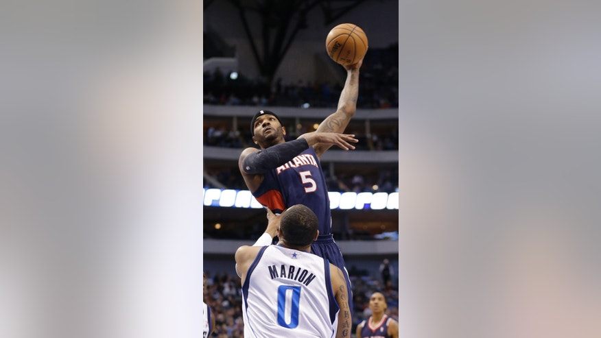 Atlanta Hawks forward Josh Smith (5) shoots over Dallas Mavericks forward Shawn Marion (0) during the first half of an NBA basketball game, Monday, Feb. 11, 2013, in Dallas. (AP Photo/LM Otero)
